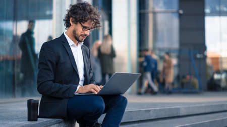 Handsome Businessman in a Suit is Sitting on Steps next to Business Center and Working on a Laptop on a Street in a City. Office People Walk By to Work. Reklamní fotografie