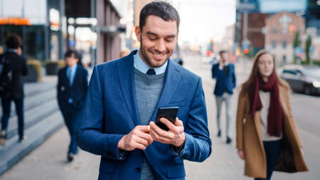 Caucasian Businessman in a Suit is Using a Smartphone on a Street in Downtown. Other Office People Walk Past. He Smiles and Looks Successful. Hes Browsing the Web on his Device.