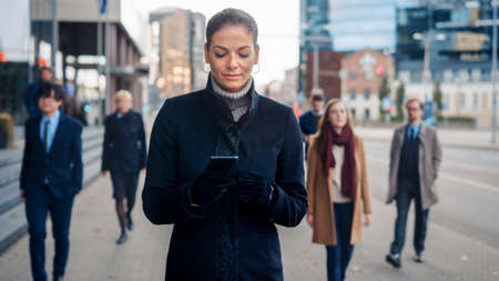 Beautiful Businesswoman in Black Coat is Using a Smartphone on a Street in Downtown. Other Office People Walk Past. She Smiles and Looks Successful. Shes Browsing the Web on Her Device.