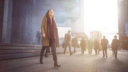 Shot of Young Smart Casually Dressed Female Office Manager Commute to Work in Morning or from Office on a Sunny Day on Foot. In the Background Pedestrians are Dressed Smartly. Shot with Warm Sun Flare