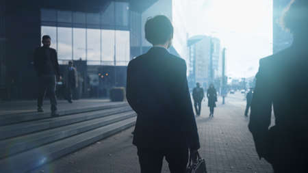 Businessman in a Suit Walking on the Street. Other Office People Commute to Work or Home. It's Early Morning or Late in the Evening. Back Shot. Urban City Lights in the Background.