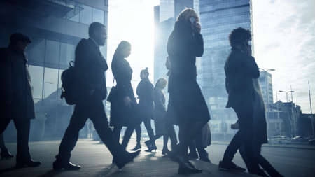 Office Managers and Business People Commute to Work in the Morning or from Office on a Sunny Day on Foot. Pedestrians are Dressed Smartly. Successful People Holding Smartphones. Cloudy Day in Downtown