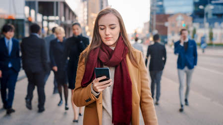 Young Smart Casually Dressed Female is Using a Smartphone on a Street. Business People and Office Managers Walk Pass on Their Way to Work. She Looks Confident while Checking Her Cell and Walking. Reklamní fotografie