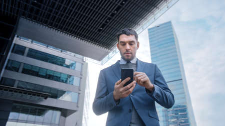 Caucasian Businessman in a Suit is Using a Smartphone on a Street in Downtown. Other Office People Walk Past. Hes Confident and Looks Successful. Hes Browsing the Web on his Device.