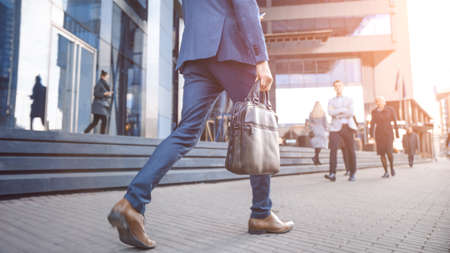 Close Up Leg Shot of a Businessman in a Suit Commuting to the Office on Foot. He's Carrying a Leather Case. Other Managers and Business People Walk Nearby. Shot with Warm Sun Flare.