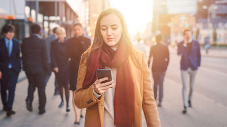 Young Casually Dressed Female is Using a Smartphone on a Street. Business People and Office Managers Walk Pass on Their Way to Work. She Looks Confident while Checking Phone. Shot with Warm Sun Flare. Reklamní fotografie