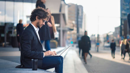 Handsome Businessman in a Suit is Sitting on Steps next to Business Center and Working on a Laptop on a Street in a City. Office People Walk By to Work. Imagens