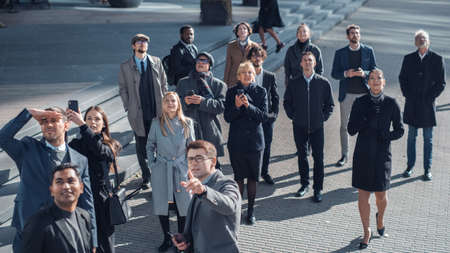 Multicultural Diverse Office Managers and Business People Suddenly Stop on the Street and Look Up. Unbelievable, Fantastic or Tragic Event Happening Live. Crowd Takes Out Smartphones and Record Video. Standard-Bild