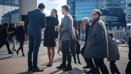 Multicultural Diverse Office Managers and Business People Walking on a Street. Female and Male Meet a Corporate Partner next to Business Center and Shake Hands. Action is Reflected in a Glass Wall.