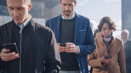 Office Managers and Businessmen are Walking in Front of a Modern Glass Office Building and Use Their Smartphones. People are Dressed Smartly and Look Successful. They are Occupied by Their Devices.