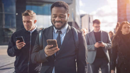 Portrait of a Smiling African American Businessman in a Suit Standing on a Street with Pedestrians. Hes Using a Smartphone. He Looks Successful. Other People Go to Work.