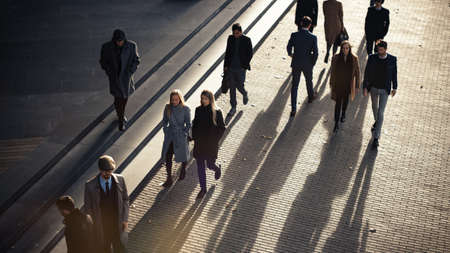 High Angle Shot of Office Managers and Business People Commuting to Work in the Morning or from Office on a Sunny Day on Foot. Pedestrians are Dressed Smartly. Successful People Holding Smartphones.