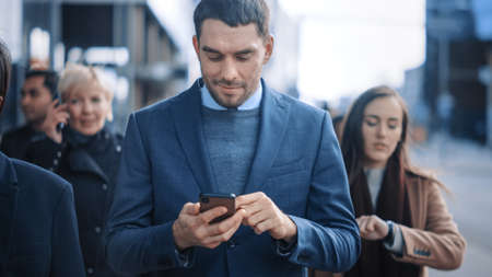 Caucasian Businessman in a Suit is Using a Smartphone on a Street in Downtown. Other Office People Commute in a Crowd. Hes Confident and Looks Successful. Hes Browsing the Web on his Device. Imagens