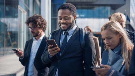Portrait of an African American Businessman in a Suit Standing on a Street with Pedestrians. Hes Using a Smartphone. He Looks Successful. Other People Go to Work.