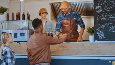 Food Truck Employee Hands Out Card Terminal to a Young Man in Leather Jacket. Indian Man is Using Contactless Bank Credit Card to Pay for Food. Street Food Truck Selling Burgers Outdoors.