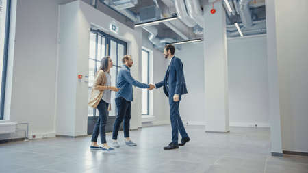 Real Estate Agent Showing a New Empty Office Space to Young Male and Female Hipsters. Entrepreneurs Meet the Broker and They Shake Hands. They Wish to Purchase or Rent.