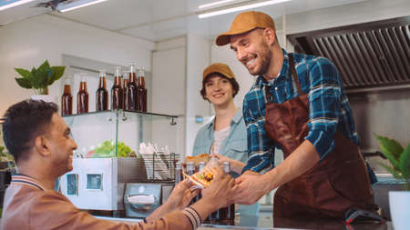 Food Truck Employee Hands Out Burger and Cold Drink to Happy Young Hipster Customer. Commercial Truck Selling Street Food in Modern Cool Neighbourhood.