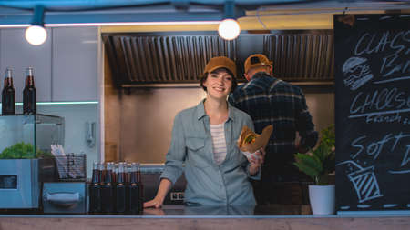 Food Truck Female Employee Hold Tasty Burger, Smiles and Looks at the Camera. Street Food Truck Selling Street Food in a Modern Neighborhood. Business Owner is Happy at Work. Brunette Wears a Cap.