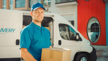 Handsome Courier Takes Cardboard Box Package out of Delivery Van Walks Through Modern Stylish Business District. Courier On the Way to Deliver Postal Parcel to a Client