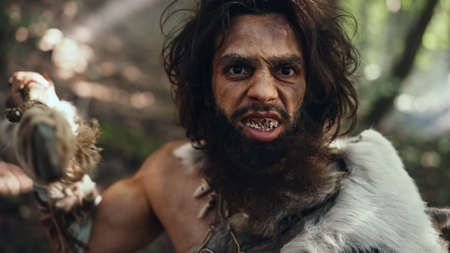 Portrait of Primeval Caveman Wearing Animal Skin and Fur Hunting with a Stone Tipped Spear in the Prehistoric Forest. Prehistoric Neanderthal Screaming, Threatening and Attacking