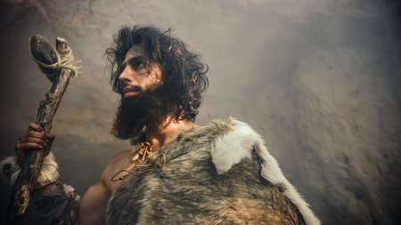 Primeval Caveman Wearing Animal Skin Holds Stone Tipped Hammer Comes out of the Cave and Looks into Prehistoric Forest, Ready to Hunt Animal Prey. Neanderthal Going Hunting into the Jungle.