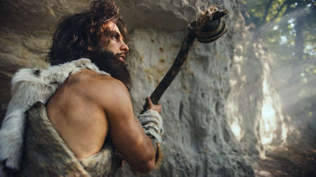 Primeval Caveman Wearing Animal Skin Holds Stone Tipped Hammer Comes out of the Cave and Looks Around Prehistoric Forest, Ready to Hunt Animal Prey. Neanderthal Going Hunting into the Jungle. Stock Photo