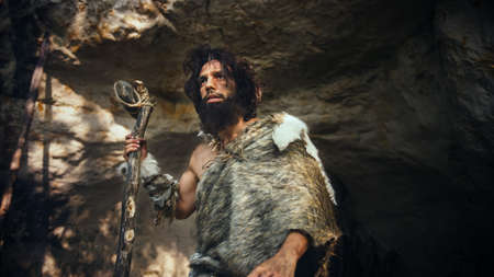 Primeval Caveman Wearing Animal Skin Holds Stone Tipped Hammer Comes out of the Cave and Looks Around Prehistoric Forest, Ready to Hunt Animal Prey. Neanderthal Going Hunting into the Jungle.