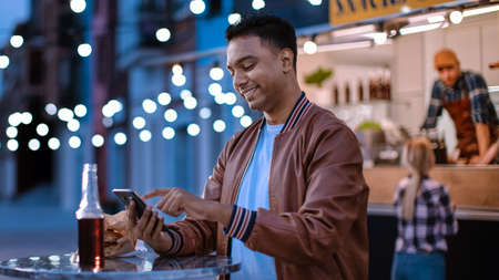 Handsome Young Indian Man is Using a Smartphone while Sitting at a Table in a Outdoors Street Food Cafe. Hes Browsing the Internet or Social Media, Posting a Status Update. Man is Happy and Smiling.