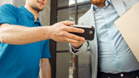 Delivery Man Gives Postal Package to a Business Customer, Who Signs Electronic Signature POD Device. In Stylish Modern Urban Office Area Courier Delivers Cardboard Box Parcel to a Man.