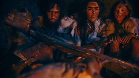 Neanderthal or Homo Sapiens Family Cooking Animal Meat over Bonfire and then Eating it. Tribe of Prehistoric Hunter-Gatherers Wearing Animal Skins Eating in a Dark Scary Cave at Night.