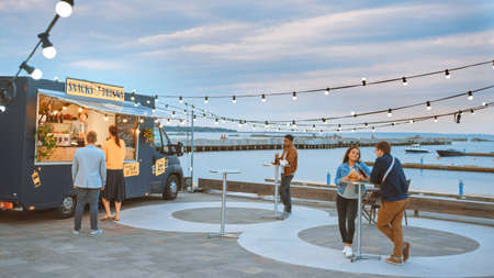 Food Truck Employee Hands Out Beef Burgers, Fries and Cold Drinks to Happy Hipster Customers. People are Eating at Tables Outside. Commercial Truck Selling Street Food in a Modern Place Near the Sea.