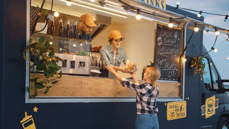 Food Truck Employee Hands Out a Freshly Made Burger and a Soft Drink to a Happy Young Female. Street Food Truck Selling Burgers in a Modern Hip Neighbourhood