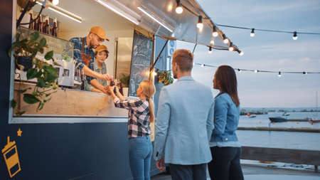 Food Truck Employee Hands Out Beef Burgers, Fries and Cold Drinks to Happy Hipster Customers. People are Eating Outside. Commercial Truck Selling Street Food in a Modern Place Near the Sea. Stock Photo