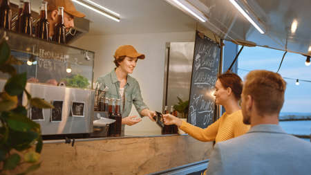 Food Truck Employee Hands Out a Freshly Made Burger to a Happy Young Female. Young Lady is Paying for Food with Contactless Credit Card. Street Food Truck Selling Burgers in a Modern Hip Neighbourhood Stock Photo