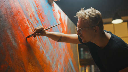 Portrait of Talented Artist Working on Abstract Painting, Uses Paint Brush To Create Daringly Emotional Modern Picture. Dark Creative Studio Large Canvas Stands on Easel Illuminated. Side View Close-up Shot