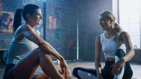 Two Beautiful Fit Athletic Girls Sit on a Floor of Industrial Loft Gym. Theyre Happy with their Training Program and Talk about Sport Achievements. Facility has Motivational Posters on the Wall.