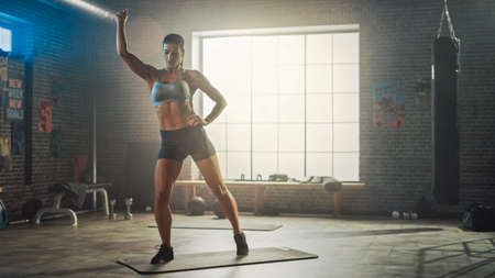 Strong and Fit Beautiful Athletic Woman in Sport Top and Shorts is Doing Standing March Exercises in a Loft Style Industrial Gym with Motivational Posters. Its Her Cross Fitness Training Workout.