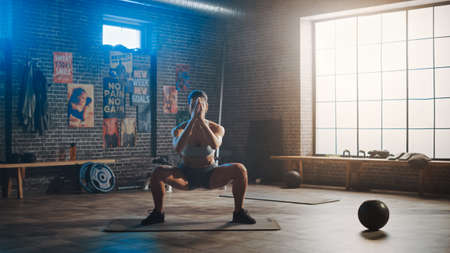 Strong and Fit Beautiful Athletic Woman in Sport Top and Shorts is Doing Squat Exercises in a Loft Style Industrial Gym with Motivational Posters. Its Part of Her Cross Fitness Training Workout.