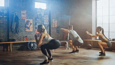 Strong Masculine Man and Two Fit Atletic Women are Doing Squat Exercises. They Workout in a Loft Gym with Motivational Posters on Walls. Its Sunny and Room has Warm Light. Part of Their Team Fitness.
