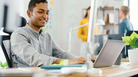 Handsome Smiling Indian Office Worker Sitting at His Desk works on a Laptop. In the Background Modern Office with Diverse Team of Young Professionals Working.