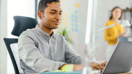 Smart and Handsome Indian Office Worker Sitting at His Desk works on a Laptop. In the Background Modern Office with Diverse Team of Young Professionals Working.