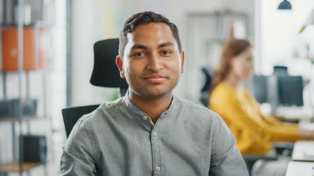 Portrait of Handsome Professional Indian Man Working at His Desk, Using Personal Computer and Smiling at the Camera. Successful Man Working in Bright Diverse Office.