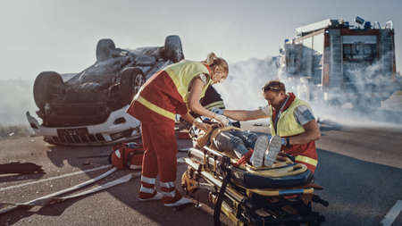 On the Car Crash Traffic Accident Scene: Paramedics Saving Life of a Little Girl Lying on Stretchers, She s given First Aid Help. Firefighter Leads Mother To Daughter. In Background Rollover Vehicle Foto de archivo