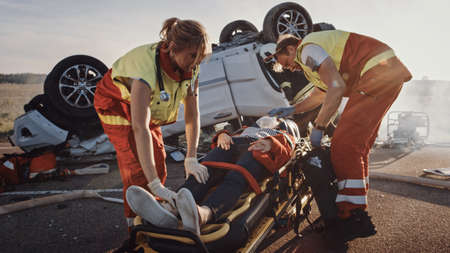 On the Car Crash Traffic Accident Scene: Paramedics Saving Life of a Female Victim who is Lying on Stretchers. They Apply Oxygen Mask and Give First Aid. In Background Rollover Vehicle