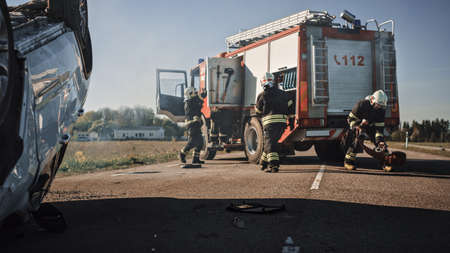 Rescue Team of Firefighters Arrive on the Car Crash Traffic Accident Scene on their Fire Engine. Firemen Grab their Tools, Equipment and, Gear from Fire Truck, Rush to Help Injured, Trapped People Foto de archivo