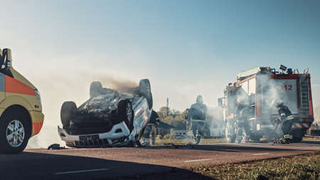 On the Car Crash Traffic Accident Scene: Paramedics and Firefighters Rescue Injured Victims Trapped in the Vehicle. Medics Use Stretchers, Perform First Aid. Firemen Grab Equipment from Fire Engine Foto de archivo