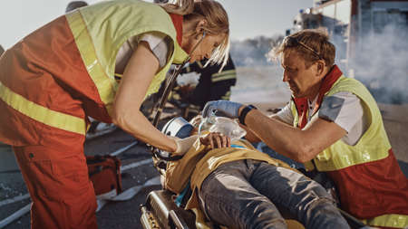 On the Car Crash Traffic Accident Scene: Paramedics Saving Life of a Traffic Accident Victim who is Lying on Stretchers. They Listen To a Heartbeat, Apply Oxygen Mask and Give First Aid Help