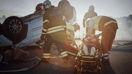 On the Car Crash Traffic Accident Scene: Rescue Team of Firefighters Pull Female Victim out of Rollover Vehicle, They Use Stretchers Carefully, Hand Her Over to Paramedics who Perform First Aid