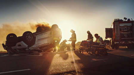 On the Car Crash Traffic Accident: Paramedics and Firefighters Rescue Injured Trapped Victims. Medics give First Aid to Female on Stretchers. Firemen Use Hydraulic Cutters Spreader to Open Vehicle Foto de archivo