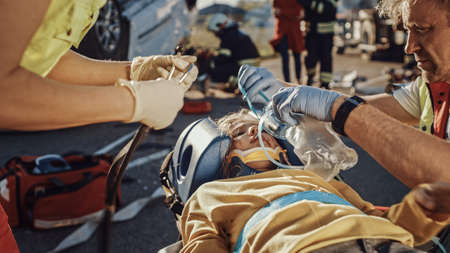 On the Car Crash Traffic Accident Scene: Paramedics Saving Life of a Traffic Accident Victim who is Lying on Stretchers. They Listen To a Heartbeat, Apply Oxygen Mask and Give First Aid Help Foto de archivo